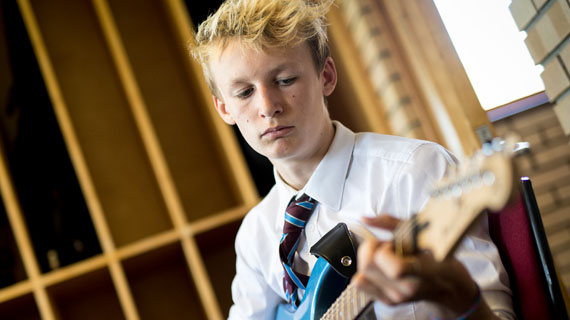 Student learning to play musical instrument