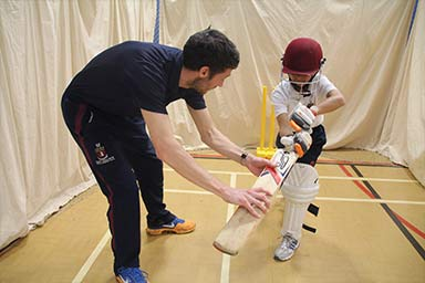A student being taught how to hold a cricket bat
