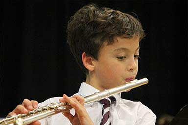 A Junior boy playing the flute