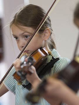 Young girls learning to play the violin