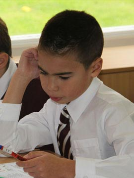 A young boy learning maths and using a calculator